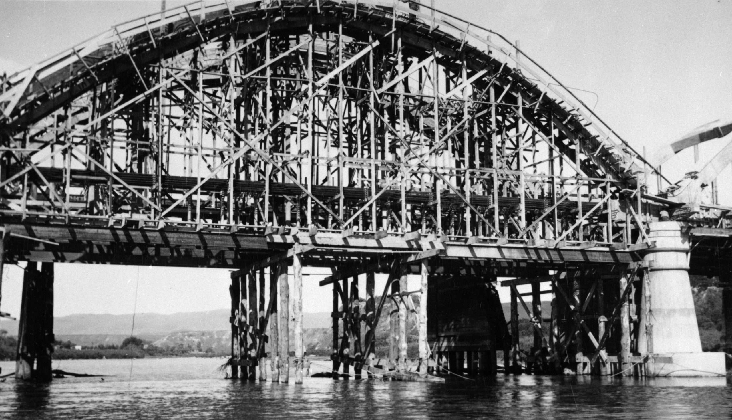 Image depicts concrete bridge surrounded by wooden scaffolding.