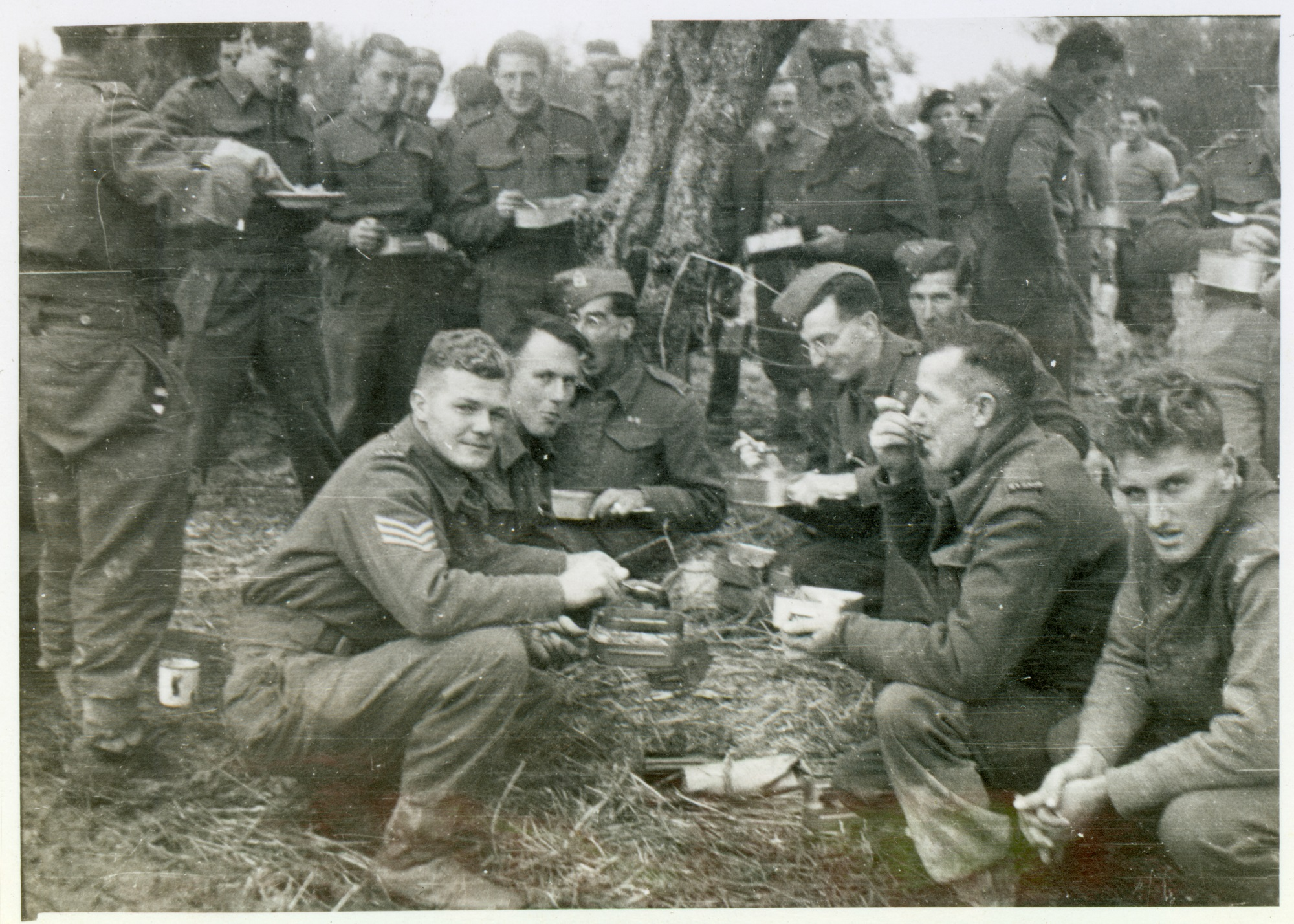 image depicts historical scene of world war two soldiers at ease, crouched in grass while eating tinned food for Christmas dinner.